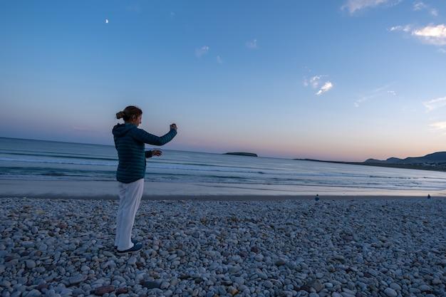 Femme de voyageur prenant une photo sur une plage rocheuse au coucher du soleil