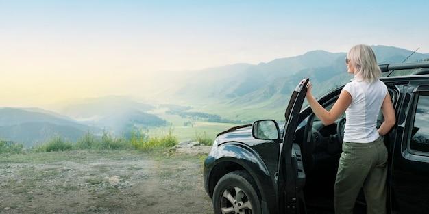 Femme voyageur regardant le coucher du soleil des montagnes, debout près de la voiture
