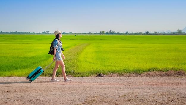 Femme voyageur remorquant des bagages et marchant sur la route.