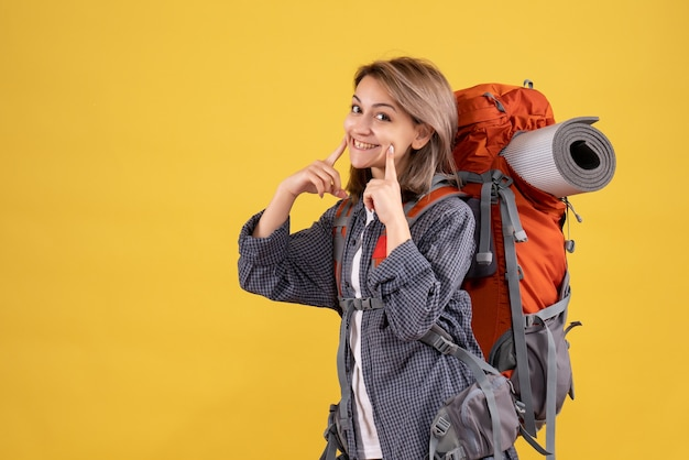Femme voyageur avec sac à dos rouge souriant
