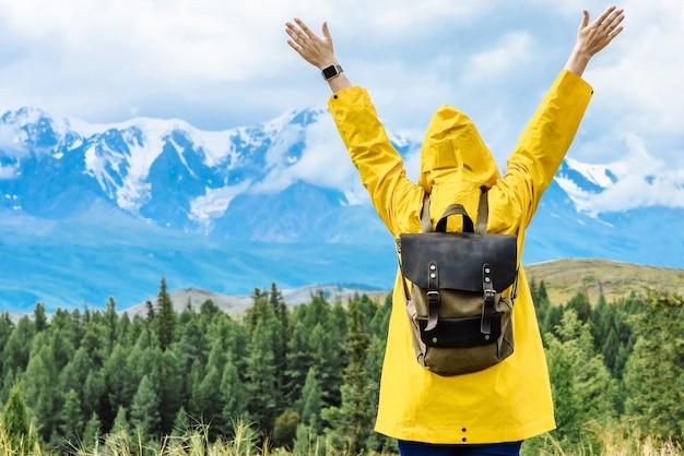 Femme voyageur avec un sac à dos se penche sur la montagne avec les mains levées