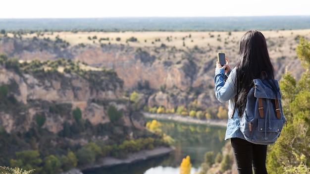 Femme de voyageur avec sac à dos et téléphone portable dans les montagnes