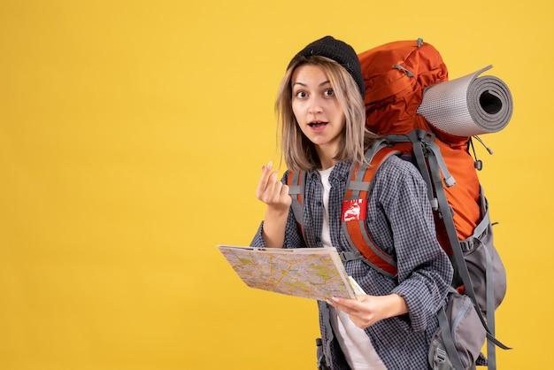 Femme voyageur avec sac à dos tenant une carte faisant de l'argent signe