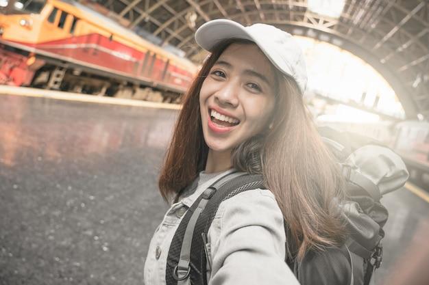 Femme voyageur avec sac à dos voyageant en prenant photo autoportrait avec smartphone.