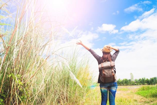 Femme voyageur se manoele et respire au champ de graminées et ciel bleu, concept de voyage errance, espace pour le texte