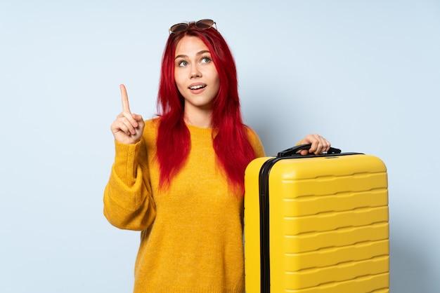 Femme voyageur tenant une valise isolée sur le mur bleu dans l'intention de réaliser la solution tout en levant un doigt
