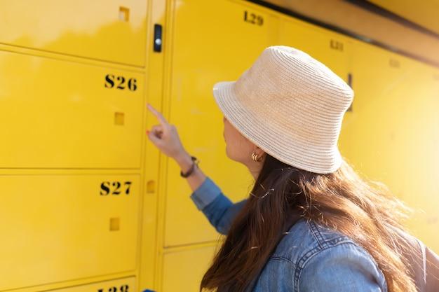 Femme voyageur utilisant le service de casier et partir en vacances en ville.