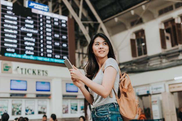 Femme voyageur utilise un smartphone devant la billetterie