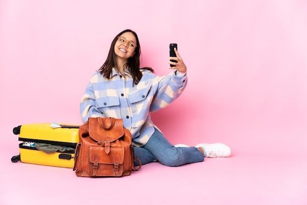 Femme de voyageur avec une valise assis sur le sol faisant un selfie
