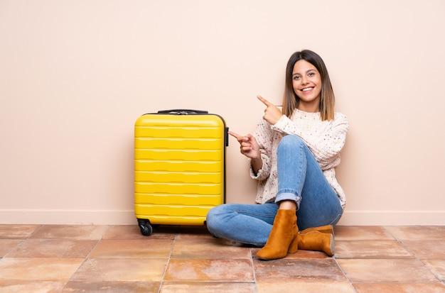 Femme de voyageur avec valise assis sur le sol, pointant le doigt sur le côté
