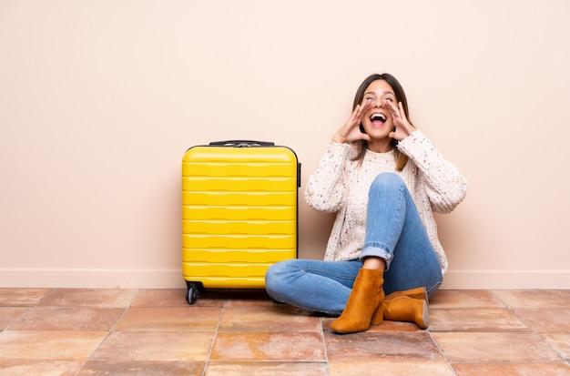 Femme de voyageur avec valise assise sur le sol en criant avec la bouche grande ouverte