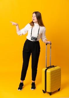 Femme de voyageur avec une valise sur fond jaune isolé