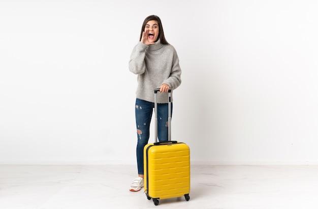 Femme voyageur avec une valise sur mur blanc isolé criant avec la bouche grande ouverte