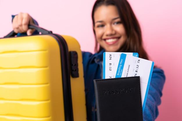 Femme voyageur avec valise sur mur isolé