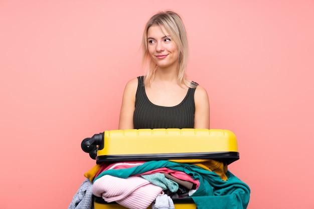 Femme de voyageur avec une valise pleine de vêtements debout et regardant sur le côté