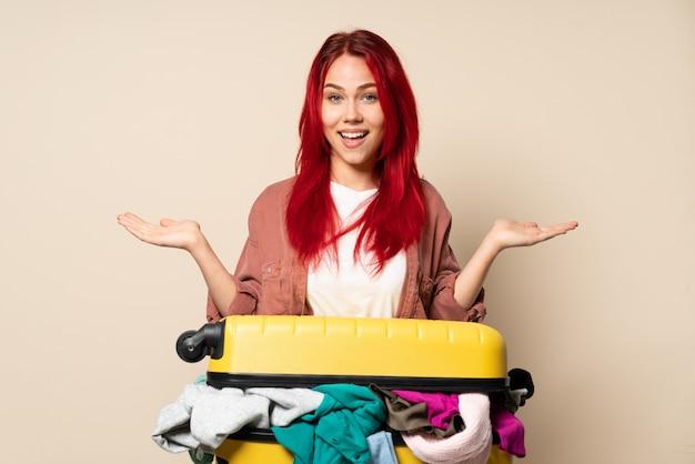 Femme de voyageur avec une valise pleine de vêtements isolé sur un mur beige avec une expression faciale choquée