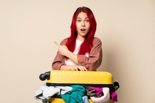 Femme voyageur avec une valise pleine de vêtements isolé sur mur beige surpris et pointant le côté