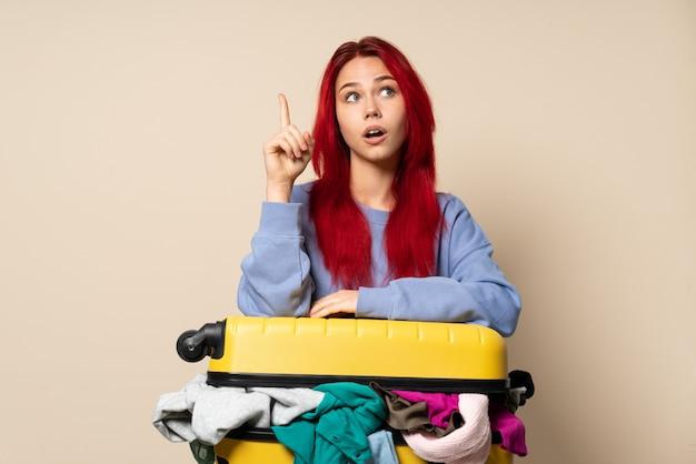 Femme de voyageur avec une valise pleine de vêtements isolés sur un mur beige ayant l'intention de réaliser la solution tout en levant un doigt