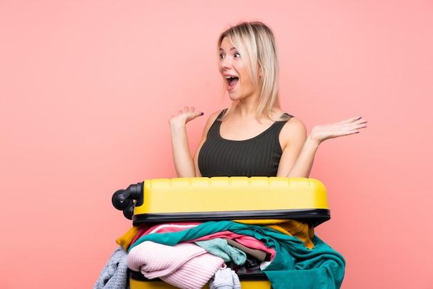 Femme voyageur avec une valise pleine de vêtements sur un mur rose isolé avec une expression faciale surprise
