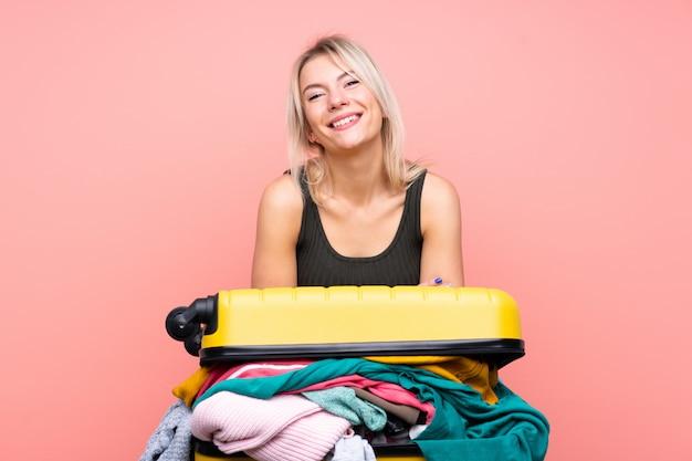 Femme voyageur avec une valise pleine de vêtements sur le mur rose isolé en riant