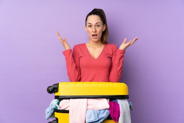 Femme voyageur avec une valise pleine de vêtements sur un mur violet isolé avec une expression faciale surprise