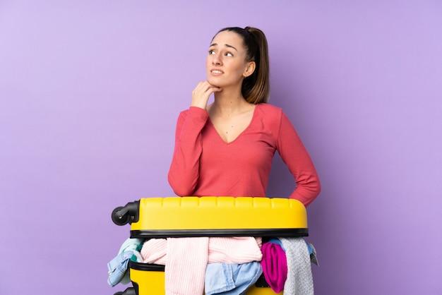 Femme voyageur avec une valise pleine de vêtements sur un mur violet isolé en pensant à une idée