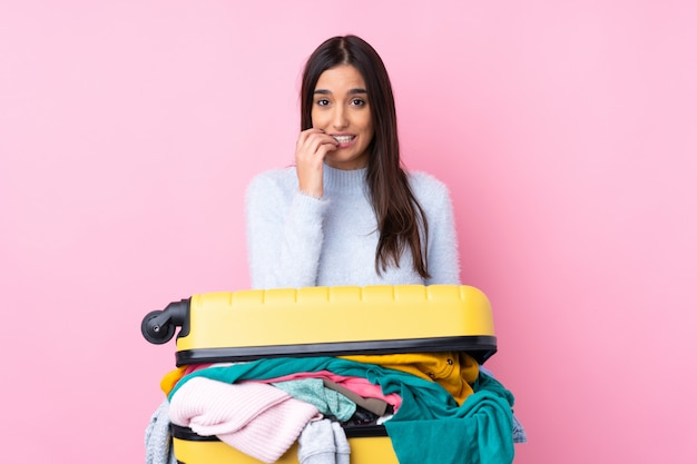 Femme de voyageur avec une valise pleine de vêtements nerveux et effrayé