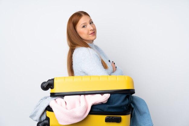 Femme de voyageur avec une valise pleine de vêtements en riant