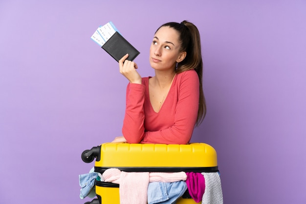 Femme de voyageur avec une valise pleine de vêtements et tenant un passeport sur un mur violet isolé