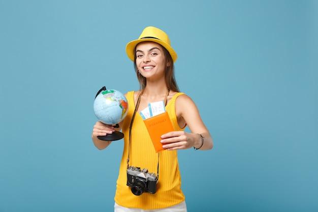 Femme de voyageur en vêtements décontractés d'été jaune et chapeau tenant des billets globe sur bleu