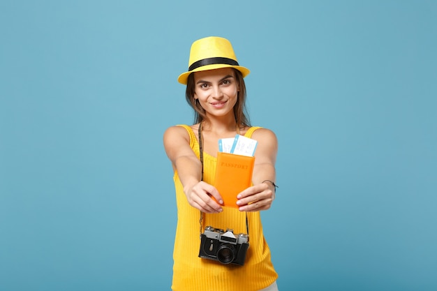 Femme de voyageur en vêtements décontractés d'été jaune et chapeau tenant une caméra de billets sur bleu