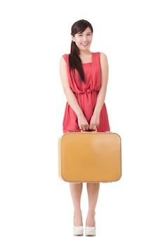 Femme voyageuse asiatique avec valise, portrait en pied avec réflexion sur fond blanc studio.