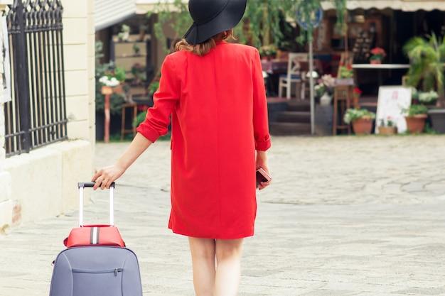Femme voyageuse au chapeau noir marchant avec valise dans la rue de la ville.