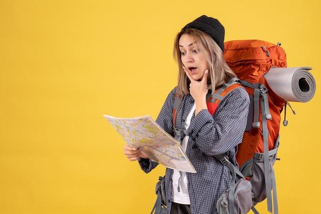Femme voyageuse avec sac à dos regardant la carte avec une grande surprise