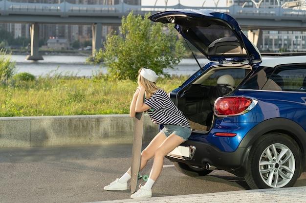 Une femme voyageuse se détend en s'appuyant sur un longboard au coffre de la voiture, une femme se reposant après la planche à roulettes en plein air