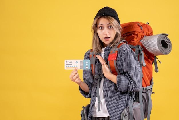 Femme voyageuse surprenante avec sac à dos tenant un billet d'avion