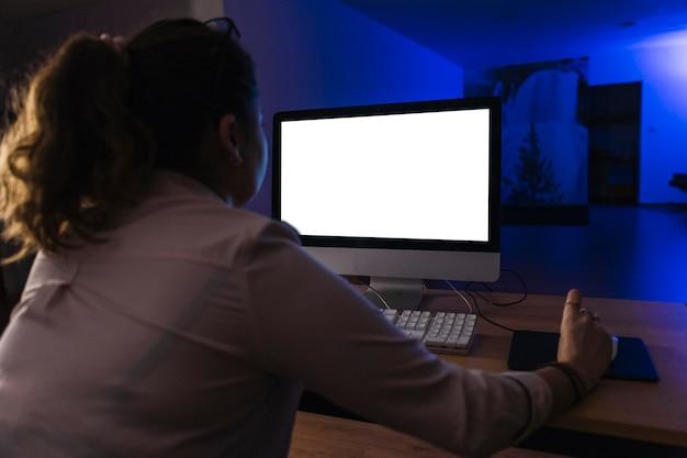 Femme vue arrière à l'aide d'ordinateur de nuit