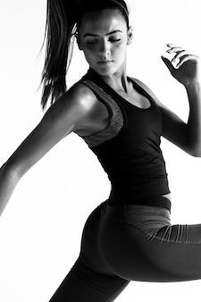 Femme vue de côté en costume de gym en niveaux de gris