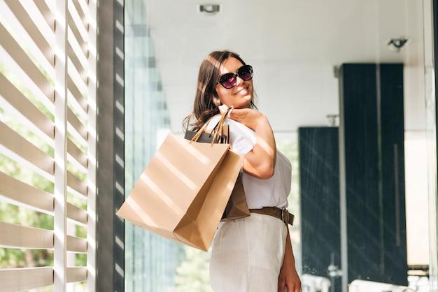 Femme vue de côté posant avec des sacs
