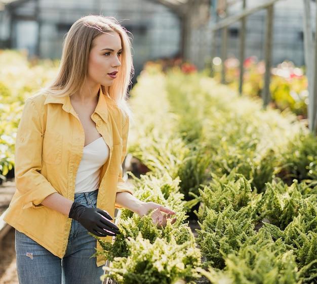 Femme vue de côté en prenant soin de fleurs