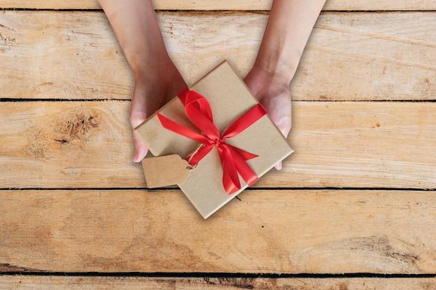 Femme vue de dessus main tenant la boîte de cadeau sur la table en bois.