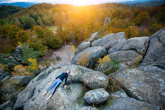 Femme vue du haut pratique le yoga et fait des asanas au sommet de la haute montagne rocheuse le soir