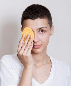 Femme vue de face à l'aide d'une éponge pour le visage
