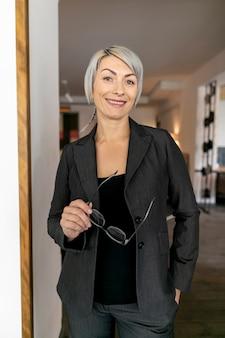 Femme vue de face en costume souriant pour caméra