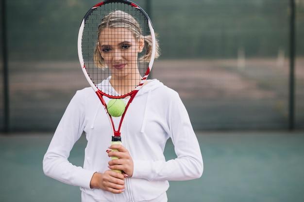 Femme vue de face couvrant le visage avec une raquette de tennis