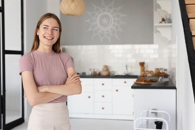 Femme vue de face, debout dans la cuisine
