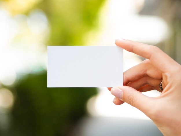 Femme vue de face, levant une maquette de carte de visite