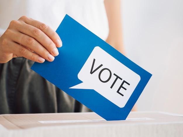 Femme vue de face mettant un message de vote dans une boîte de près