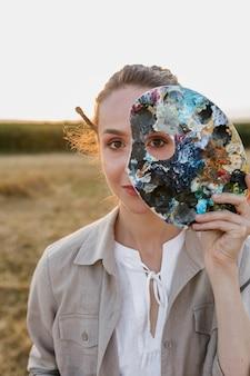 Femme vue de face avec palette de peinture