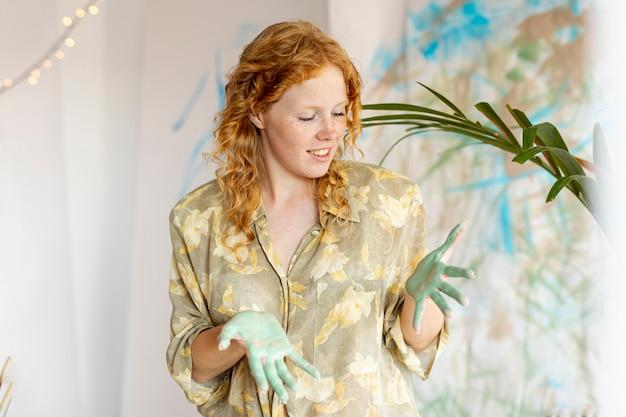 Femme vue de face avec de la peinture sur les paumes